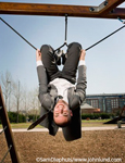 A man in a suit playing on kids playground equipment. The silly funny picture shows a businessman smiling and having fun in a child's playground setting.